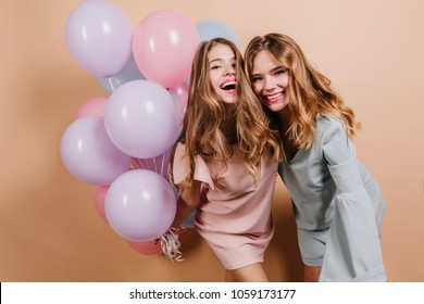 Beautiful long-haired girls joking at birthday party. Graceful young ladies with balloons preparing for festive.