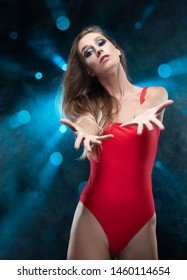 A beautiful long-haired slim girl wearing a red body, dancing, gives us her hands against the background of spots of light from which blue rays shine in the smoke. Advertising and commercial design