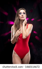 A beautiful long-haired slim girl wearing a red bodysuit sensually touches her face with her hands, standing against the background of spots of light from which mauve rays shine in the smoke