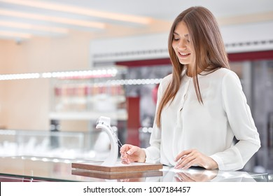 Beautiful long-haired woman wearing a pretty white blouse is looking at the costly necklace in a fashionable modern jewelry store with glass counters and smiling to herself.
