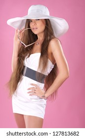 Beautiful long-haired woman in the white dress and a big hat