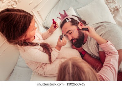 Beautiful look. Nice peaceful man sleeping in his bed while being painted by his daughters