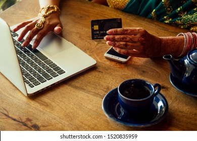 beautiful looking indian young girl in green sari working on laptop and using credit ATM card payment online, sitting in cafe / remote work and freelance.online shopping sale