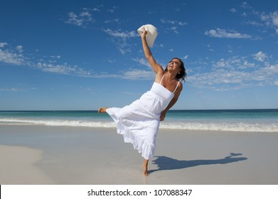 Beautiful looking mature woman in white summer dress joyful at beach holiday, isolated with ocean and blue sky as background and copy space.