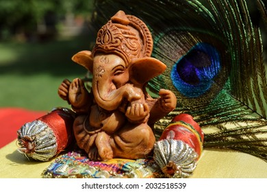 Beautiful lord Ganesha idol worshipped during Ganesh chaturthi festival with peacock feather in background. Sitting Ganpati with pillows and bolsters during Vinayaka chavithi