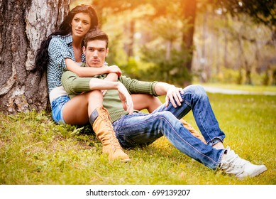 Beautiful lovely couple sitting on the grass next to the tree and enjoying in sunny park in autumn colors.