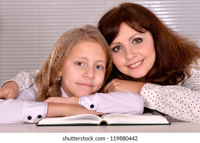 beautiful lovely smiling girl with her mother  with a book