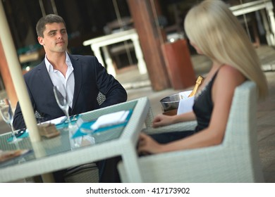 Beautiful, lovely, young couple sitting and talking in restaurant. Nice dating of friends or married couple.
