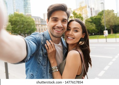 Beautiful lovely young couple walking at the city streets, hugging while taking a selfie