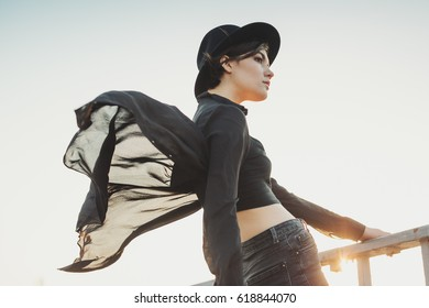 Beautiful lovely young stylish woman portrait. Black clothes, sky and sunset sun.  Big city Poets.  Bright orange sunset backlight Glares and flares.