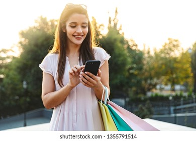 Beautiful lovely young woman with long brunette hair wearing dress walking outdoors, using mobile phone, carrying shopping bags