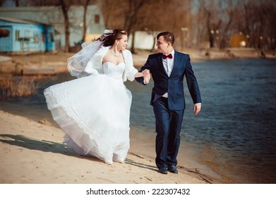 Beautiful loving couple of bride and groom is enjoying their wedding day outdoor in the park.