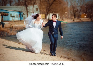 Beautiful loving couple of bride and groom is enjoying his wedding day outdoor.