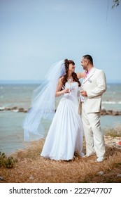 Beautiful loving couple of bride and groom is enjoying his wedding day outdoor in the park.