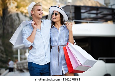 Beautiful loving couple carrying shopping bags and enjoying together.