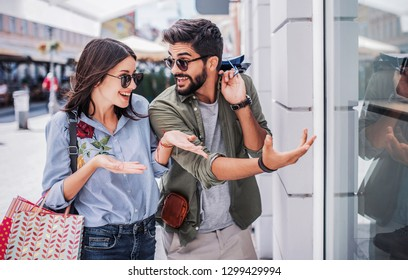 Beautiful loving couple enjoying in shopping, having fun together in the city. Consumerism, love, dating, lifestyle concept