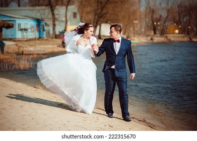 Beautiful loving couple of funny bride and groom is enjoying his wedding day outdoor in the park.