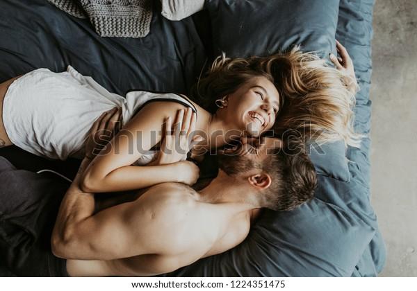 ベッドでキスをする美しい愛し合いの夫婦