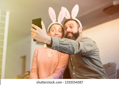 Beautiful loving couple making selfie on smartphone with pink rabbit ears on head. Happy family preparing for Easter
