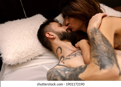 Beautiful loving couple Naked hug kissing in bed near the window in the morning . Romantic intimate lifestyle Love story of shirtless tattooed strong beard man with a sensual woman in loft apartment