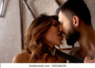 Beautiful loving couple Naked hug hot erotic kissing behind concrete wall . Romantic intimate dominant sexual bondage foreplay of tattooed strong beard man with a sensual sexy woman in loft apartment