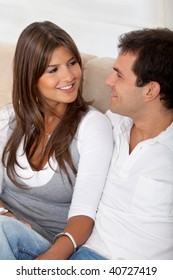 beautiful loving couple portrait sitting at home smiling