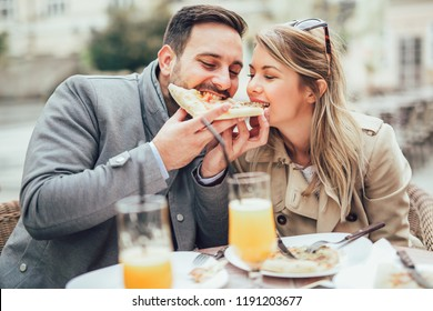 Beautiful loving couple sitting in outdoor cafe and eating pizza. Lifestyle concept