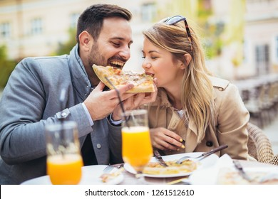 Beautiful loving couple sitting in outdoor cafe and eating pizza.