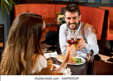 Beautiful loving couple is spending time together and  toast the glasses in modern restaurant