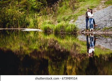 Beautiful loving couple standing by the lake outdoors