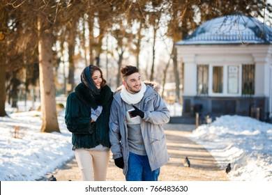 Beautiful loving couple walking in the winter park