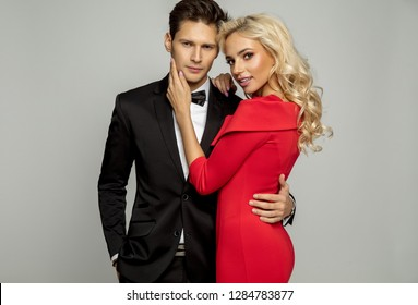 Beautiful loving couple wearing evening outfit isolated over gray background