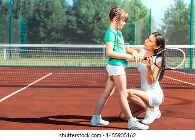 Beautiful loving mommy. Dark-haired girl listening to her beautiful loving mommy before playing tennis
