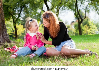 beautiful loving mother and little girl resting in park