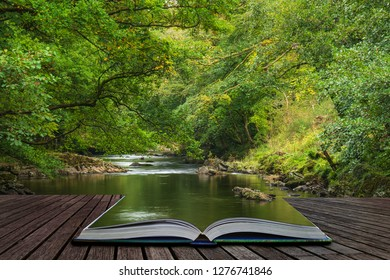 Beautiful lush green riverbank with river flowing slowly past calm landscape coming out of pages of open story book