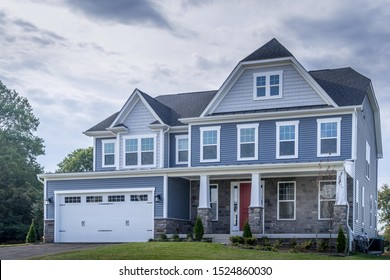 Beautiful luxury American colonial traditional estate model home,hung sash windows,  w/ two car garage, covered porch, blue horizontal vinyl lap siding, fiber cement shingle gable roof, curb appeal
