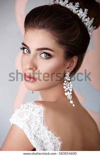 Beautiful Luxury Bride with diamond jewelry Fashion portrait studio. Gorgeous young bride with wedding makeup and long dark hair in bridal lace dress isolated