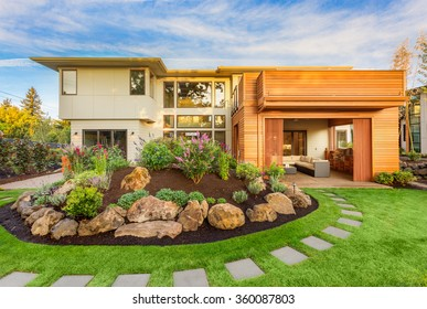Beautiful Luxury Home Exterior  with Balcony and Green Grass on Sunny Afternoon