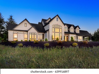Beautiful Luxury Home Exterior at Night with Sunset Reflection in Windows