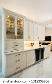 Beautiful luxury home kitchen bar with white cabinets and wine cooler.