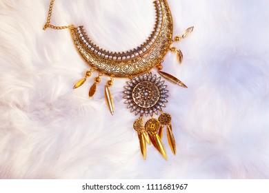 beautiful luxury jewel with filigrane ornaments lying on white fur.