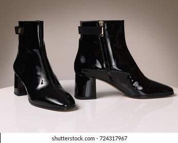 Beautiful luxury leather women's black boots, heel, on a beige background
