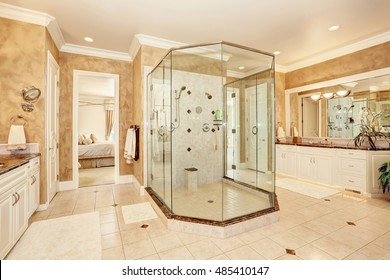 Beautiful luxury marble bathroom interior in beige color. Large glass walk in shower and two vanity cabinets. Northwest, USA