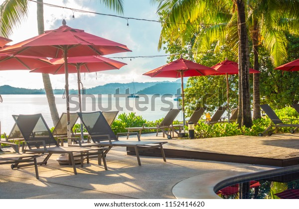 Beautiful luxury outdoor swimming pool with umbrella and chair in hotel and resort for travel and vacation