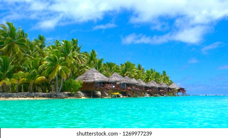 Beautiful luxury overwater villas face the stunning turquoise ocean water in the idyllic Cook Islands. Picturesque shot of holiday resort accommodation on the picturesque tropical beach in Aitutaki.