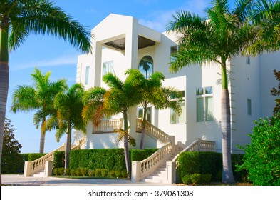 Beautiful luxury residential home with front stairways and lush green palm trees against a blue morning sky