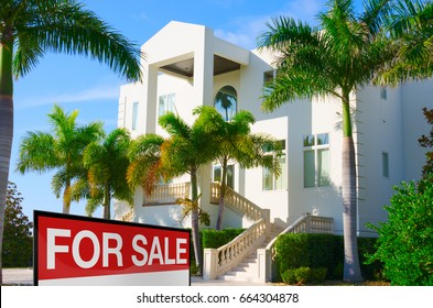 Beautiful luxury residential home with front stairways and lush green palm trees against a blue morning sky with a bright FOR SALE sign in the front yard.