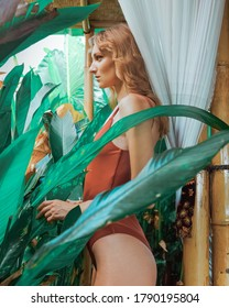 Beautiful luxury slim girl in a swimsuit posing in garden. Sexy tanned girl ginger hair girl, flat stomach, perfect figure. Vogue Style photo in Balinese taste with relaxing warm tones.