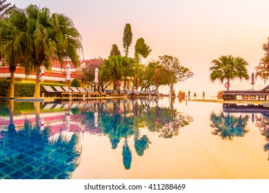 Beautiful luxury umbrella and chair around swimming pool in hotel resort at Sunset times - Vintage Filter and Boost up Color Processing