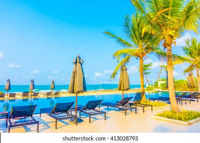 Beautiful luxury umbrella and chair around outdoor swimming pool in hotel resort neary sea and beach - Boost up color Processing style